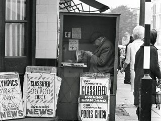 Man in evening standard stall 1950s London black and white street picture