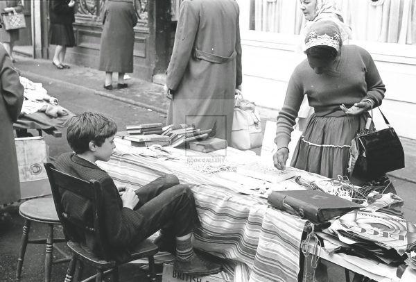Boy sat at brick a brac market stall Portobello road market