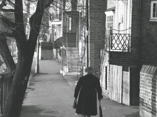 old lady walking with 1950s umbrella in hand