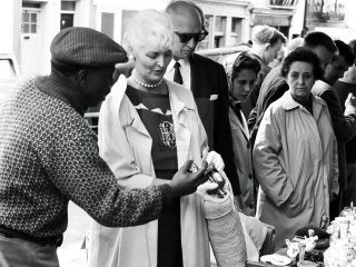 wealthy couple buying antiques at market London 1950s