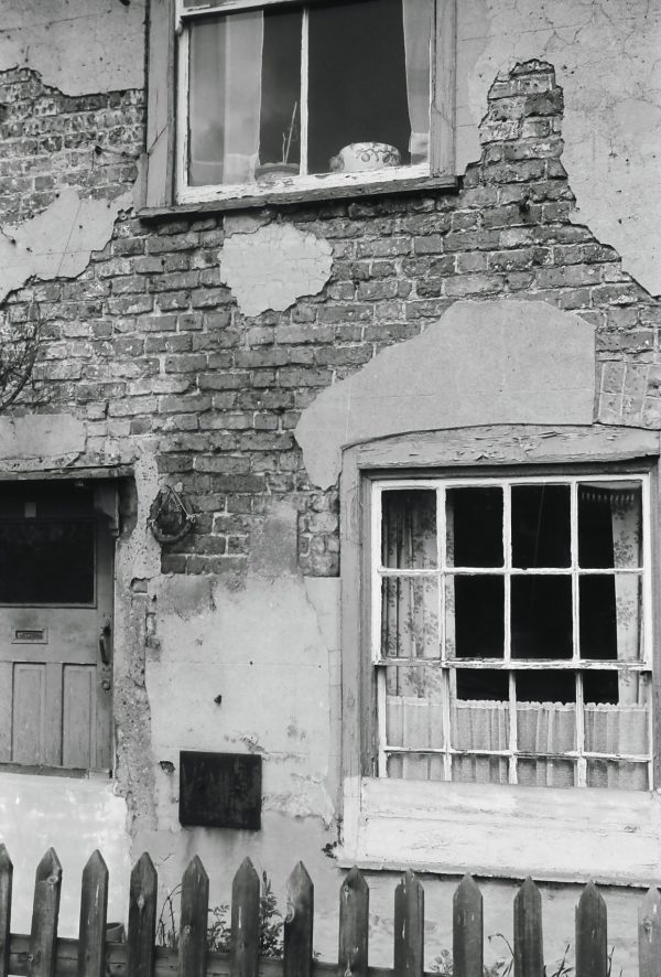 Front of run down house in 1950s black and white photography