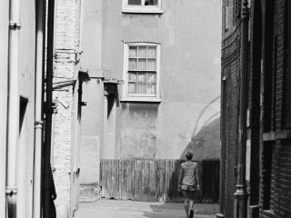 Girl walking down alleyway in 1950's London