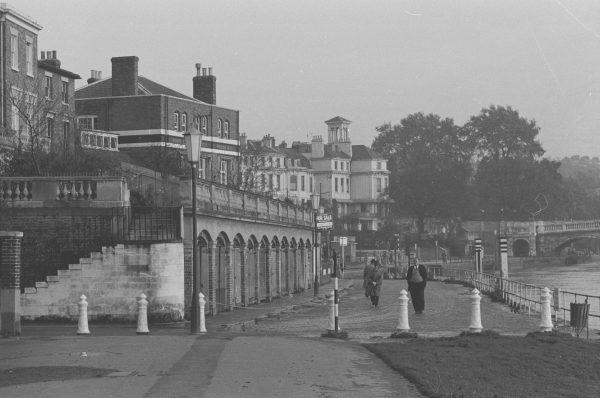 couple walking along London riverside 1950s